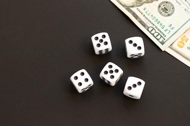 Кубики и размытые 100, 50 долларов сша на черном. фортуна, игровая зависимость. игра в куб с числами. предметы для настольных игр. плоская планировка, вид сверху, копия пространства.