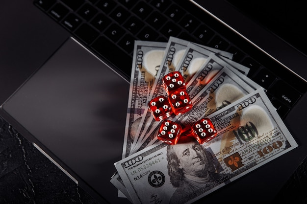 노트북의 키보드에 주사위와 달러 지폐. 온라인 카지노 및 도박 개념