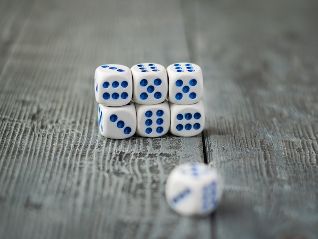 Dice are stacked in a pile on a wooden dark table.