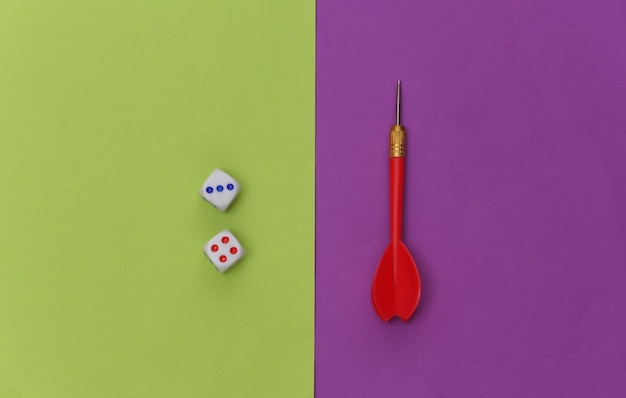 Dice and darts on purple green background. top view