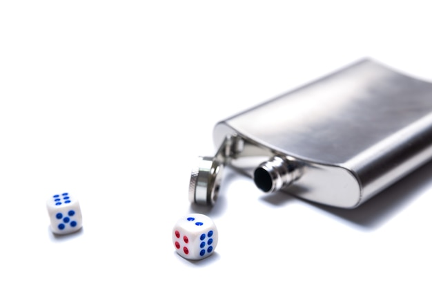 Dice and open metal flask for alcohol on a white background
