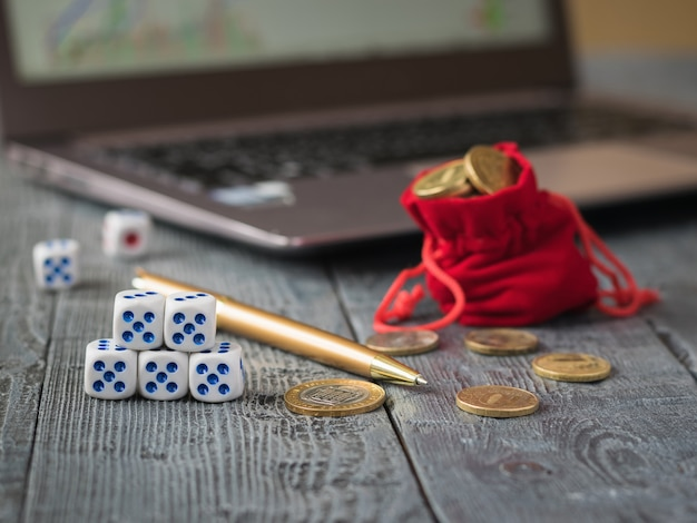 Dice and a pile of coins in front of a laptop with business schedules.