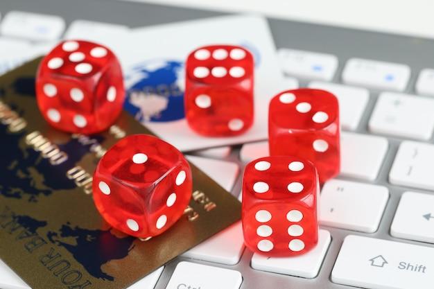 テーブルのオンラインギャンブルの概念にプラスチック製のクレジットバンクカードとコンピューターのキーボードをさいの目に切る