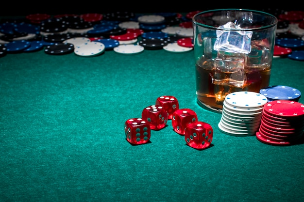 Dice; poker chips and glass of whiskey on gambling table