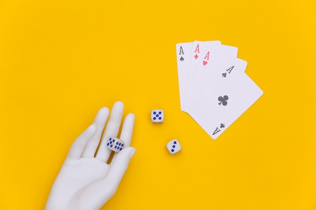 Dice in a white mannequin hand and four aces on a yellow background. top view