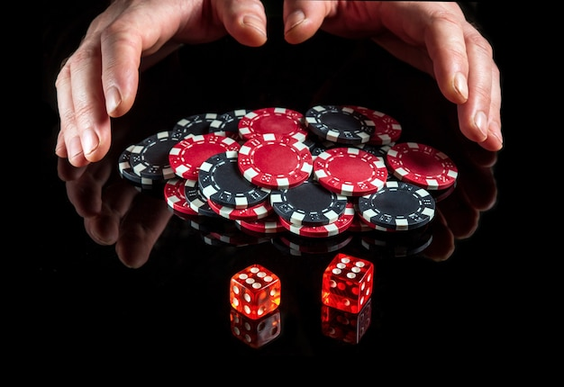 The dice with the maximum winning combination of twelve in craps on the black table and the hands take the chips from the win