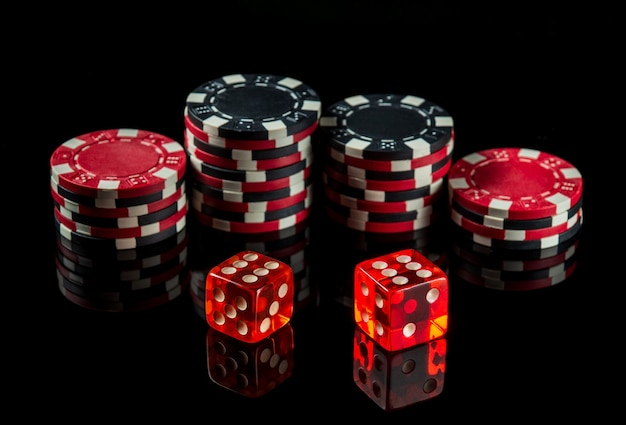 Dice with a maximum winning combination of twelve in poker on a black table and chips in the background