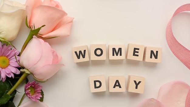 ピンクの花とリボンで飾られた白いテーブルの背景に「女性の日」という言葉でサイコロ