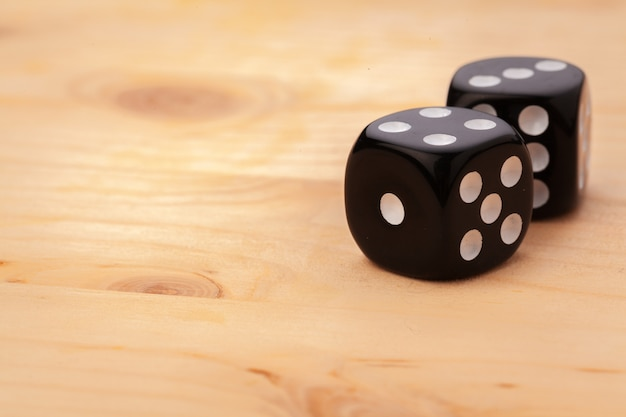 Dice on wooden table for casino games.