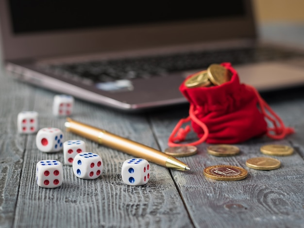 Dice on a wooden table with a notebook, pen and money. workplace.