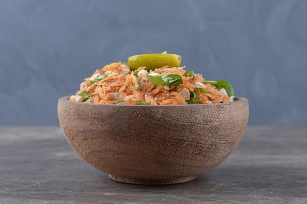 나무 그릇에 깍둑썰기한 당근과 야채 샐러드입니다.