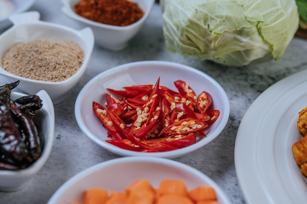 Diced carrots, dried chilies, roasted rice, chili, and cabbage are placed on a cement floor