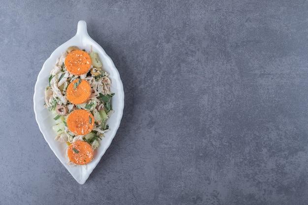 잎 모양의 접시에 깍둑썰기한 치킨 샐러드.