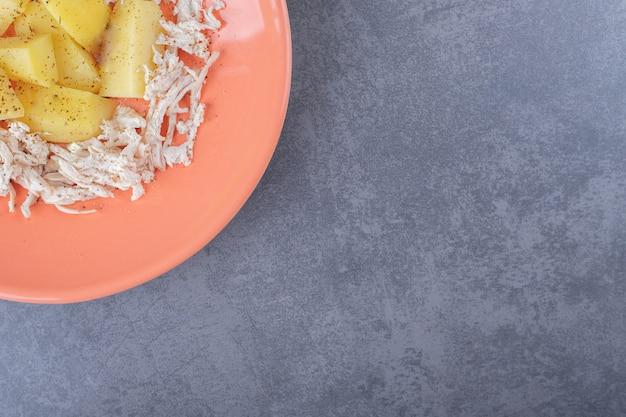 오렌지 접시에 삶은 감자와 diced 치킨입니다.