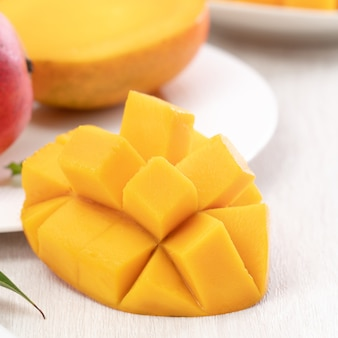 Diced fresh mango fruit on a white plate with leaves over wooden table background