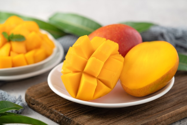 Diced fresh mango fruit on a white plate over wooden cutting board with leaves on gray table background