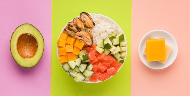 Салат из кубиков тыквы рядом с авокадо и сыром на зеленом, желто-фиолетовом фоне