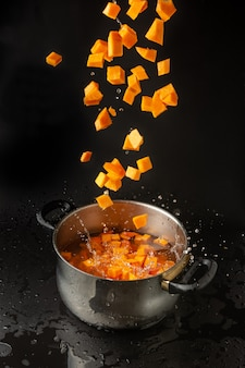 Diced pumpkin falling in a boiling pot, isolated on black