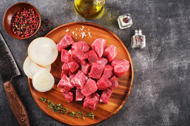 Diced raw beef on an wooden board, spices, herbs and vegetables on dark grey background. raw ingredients for goulash. top view.