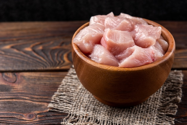 Diced raw chicken breast or fillets on dark wooden background.