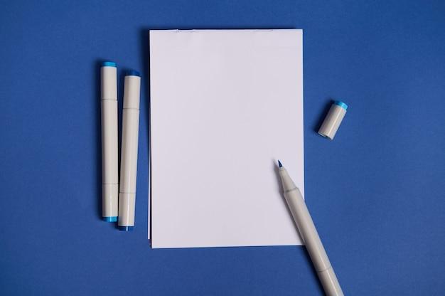 Двухцветная плоская композиция с акварельными маркерами или фломастерами с белым пустым листом бумаги с копией пространства, изолированной на синем фоне.