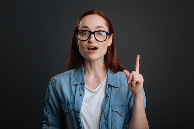 And did you know that. persistent diligent nice girl pointing her finger up while explaining her point and standing isolated on grey background