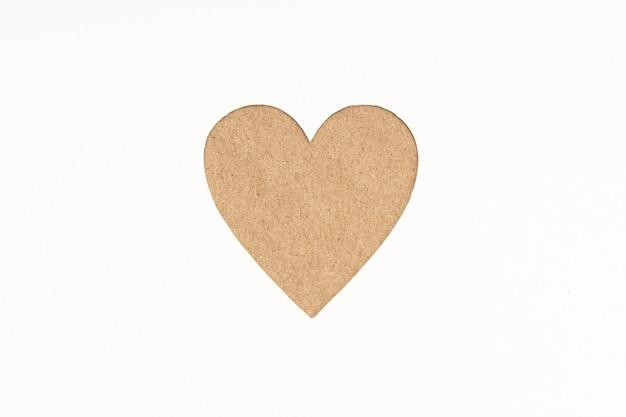 白い紙の背景に分離されたダイカット段ボールハート型。愛の概念