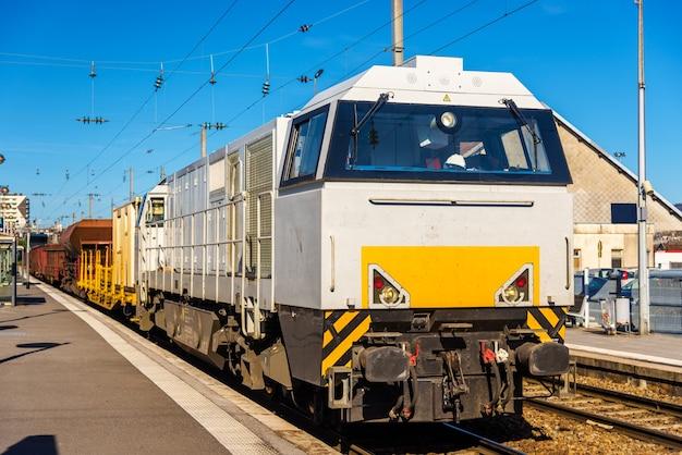 Тепловоз буксирует грузовой поезд на станции безансон - франция