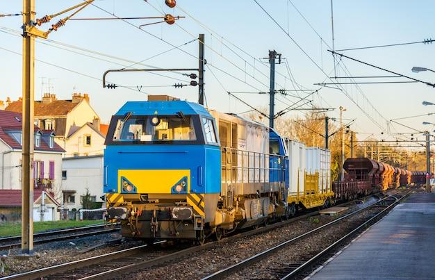 Тепловоз буксирует товарный поезд на станции монбельяр - франция