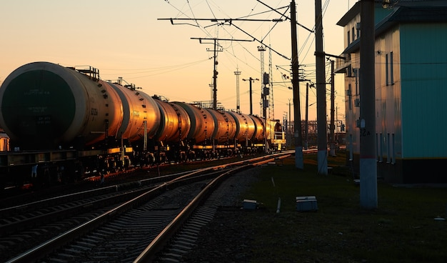 Diesel locomotive with wagons at the railway station in the morning dawn light