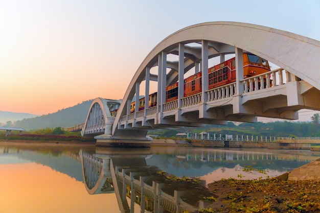Diesel train passing the white railway bridge during morning sunrise.