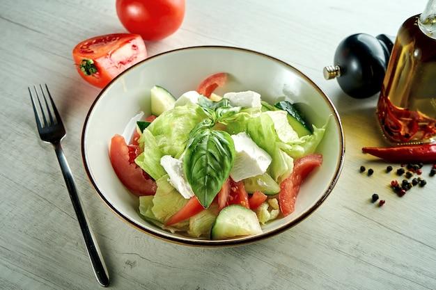 Диетический и вкусный овощной салат с сыром фета, подается в голубой миске на деревянном столе. здоровая пища.