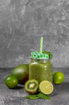 다이어트와 해독 개념. 어두운 배경 위에 시금치, 바나나, 키위, 사과 주스와 녹색 스무디. 깨끗한 식사와 건강한 음식.