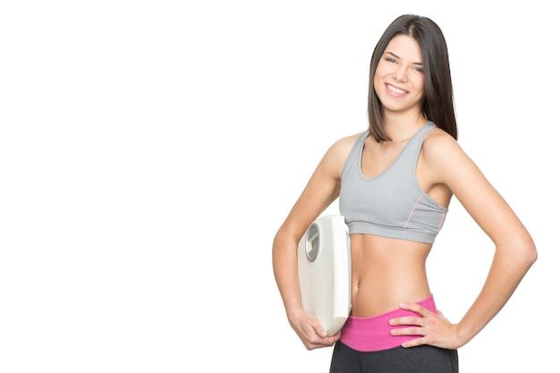 食事療法と運動。スケールを保持し、側面の白いコピースペースで幸せに分離された笑顔の若いフィットネス女性の肖像画