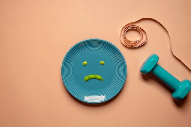 다이어트 및 건강 관리 개념. 체중 감량을 시도하십시오. 접시에 녹색 콩입니다. 불행한 음식. 덤벨과 부드러운 줄자로 둘러싸여 있습니다. 평면도