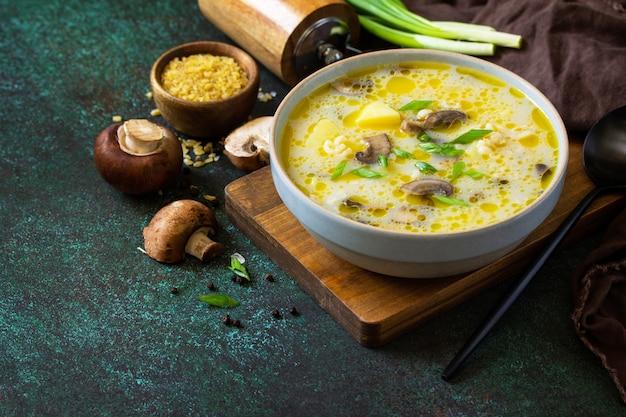 食事と健康的な食事のコンセプトです。暗い石の背景にブルガーとロイヤルマッシュルームクリームスープ。コピースペース。