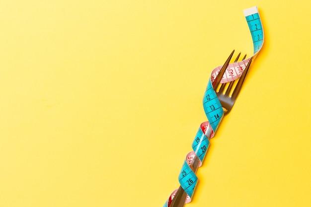 黄色の背景に巻尺で包まれたフォークでダイエットと健康的な食事の概念。コピースペースのある減量の上面図。