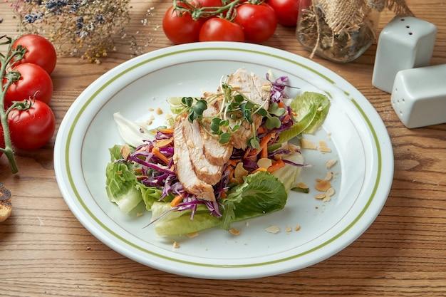Диета и здоровый салат с индейкой, овощами и капустой, подается в белой тарелке на деревянном столе. еда в ресторане