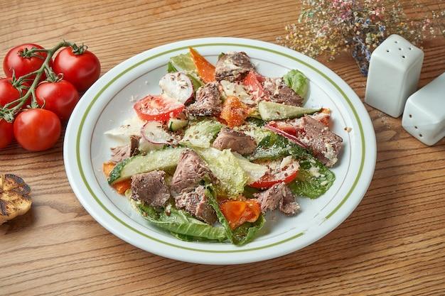 Диетический и полезный салат с телятиной, овощами и помидорами, пармезаном, подается в белой тарелке на деревянном столе. еда в ресторане