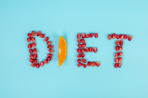 Diet arrangement of fruit pomegranate seeds and orange on blue background
