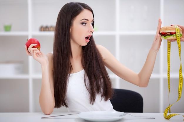 ダイエット。果物とジャンクフードの間を選択する美しい若い女性