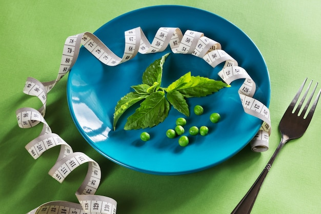 Diet blue plate with centimeter, fork and basil