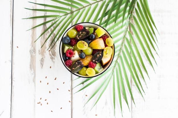 Диетический завтрак. фруктовый салат с семенами льна. концепция вегетарианской пищи.