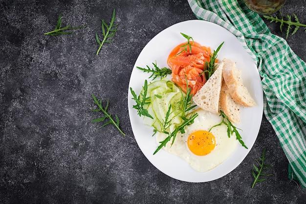 Диетический завтрак. салат из соленого лосося с зеленью, огурцами, жареным яйцом и хлебом. вид сверху, сверху
