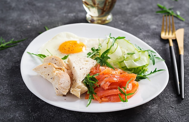 Диетический завтрак. салат из соленого лосося с зеленью, огурцами, жареным яйцом и хлебом.