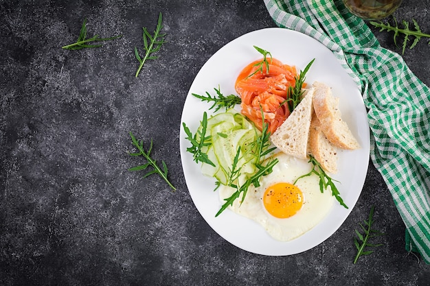 Diet breakfast. salt salmon salad with greens, cucumbers, fried egg and bread.  top view, overhead