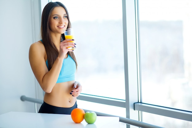 Diet. close-up on fitness young woman drinking orange smoothie in kitchen