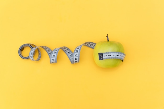 Diet concept. apple and tape measure on yellow background