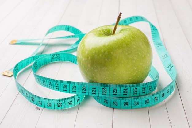 Diet concept. green apple and measuring tape on a white table.