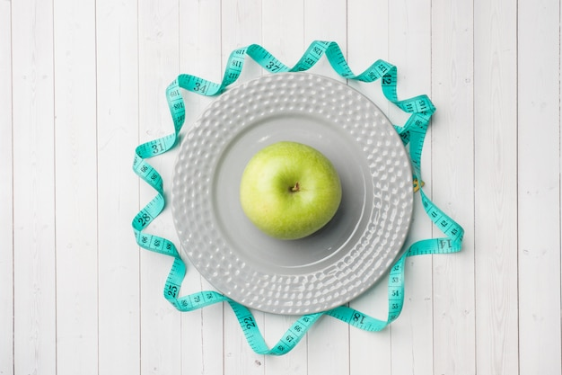 Diet concept. green apple on a plate and tape centimeter on a white table.